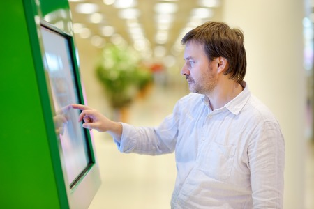 withdrawing: Middle age man in airport or shopping mall
