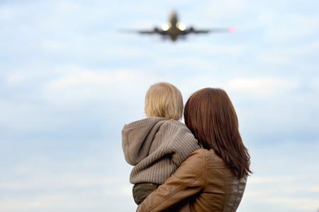 背景に飛行機で hes 幼児の息子を保持している若い母親