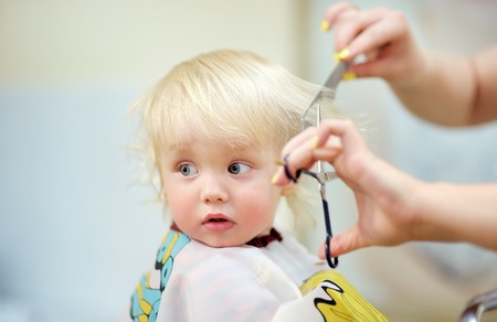 Close up portrait of toddler child getting his first haircut Foto de archivo