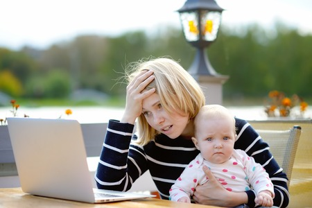 Tired young mother working oh her laptop and holding 6-month daughter Standard-Bild