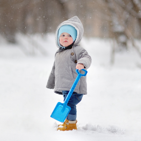 happy baby: Winter portrait of beautiful toddler boy playing with snow Stock Photo
