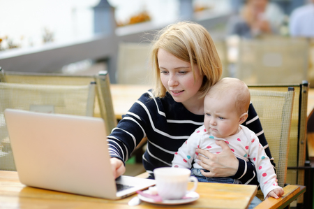 Young mother with her adorable baby girl working or studying on her laptop in outdoor cafe
