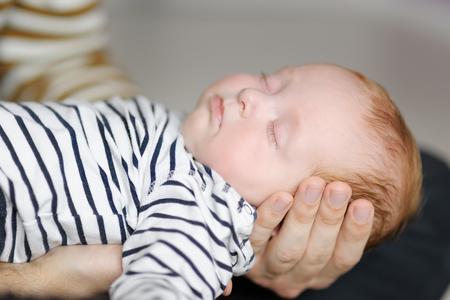 recien nacido: Padre joven que detiene a su pequeño bebé recién nacido dulce