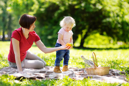 babysit: Beautiful middle aged woman and her adorable little grandson having a picnic in sunny park