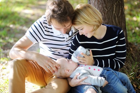 nude boy: Happy parenthood: young parents with their sweet baby girl in sunny park, focus on baby face