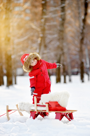 to steer a sledge: Portrait of beautiful toddler boy having fun in winter park Stock Photo