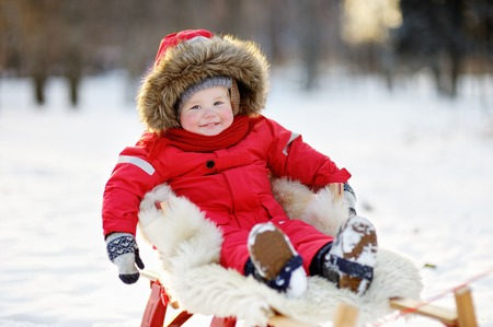 to steer a sledge: Winter portrait of beautiful toddler boy Stock Photo