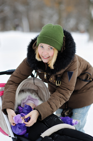 clothe: Young mother clothe warm mitten at her little daughter in winter park
