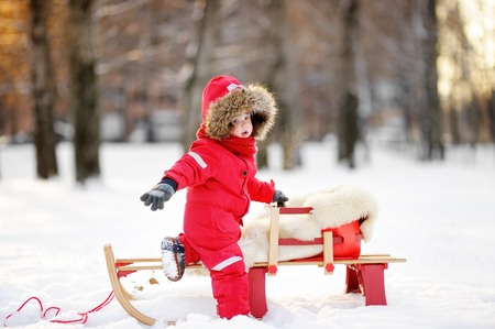 to steer a sledge: Portrait of beautiful toddler boy having fun in winter Stock Photo