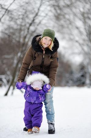 padres e hijos felices: El pequeño bebé está aprendiendo a caminar. Mujer joven con su muchacha del niño en el parque de invierno