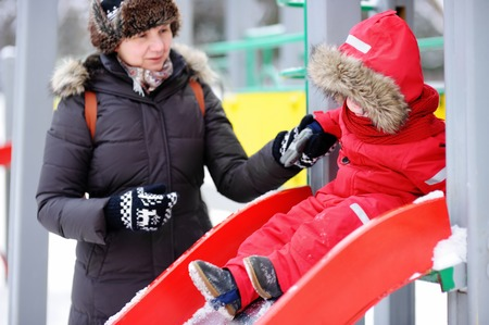 babysit: Beautiful middle aged woman and her adorable little grandson at the playground