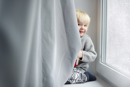 kids having fun: Toddler boy playing on the window sill at home