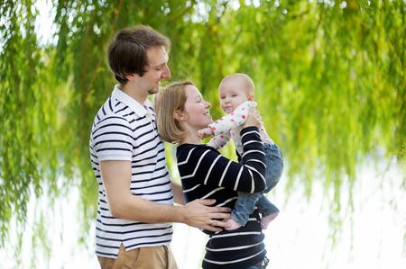nackter junge: Gl�cklich Elternschaft: junge Eltern mit ihrem s��en Baby ein M�dchen im sonnigen Park