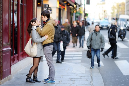 cite: PARIS, FRANCE - NOVEMBER 22, 2015: Young dating couple embrace on a street of Paris, France Stock Photo