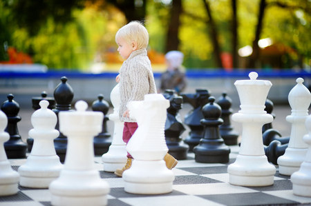 pawn to king: Toddler boy playing giant chess outdoors