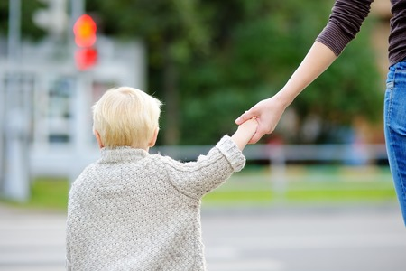 cross street with care: Mother and her toddler son crossing the street on the crosswalk Stock Photo