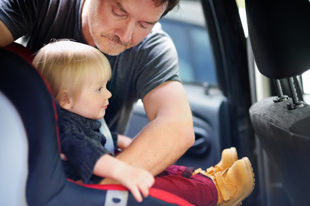 fragile: Middle age father helps his toddler son to fasten belt on car seat, focus on father