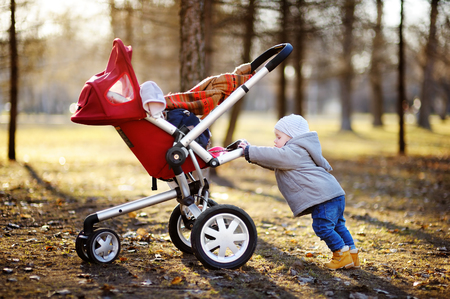 shove: Beautiful toddler boy playing with his stroller during walking outdoors at the warm spring day