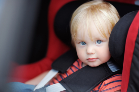 sad cute baby: Portrait of toddler boy sitting in car seat Stock Photo