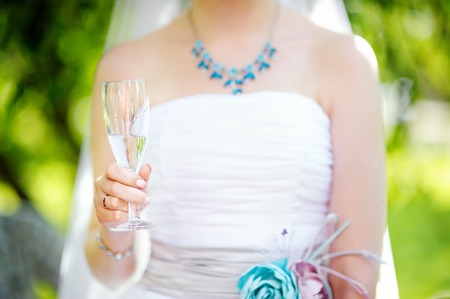 still water: Bride holding champagne glass with still water Stock Photo