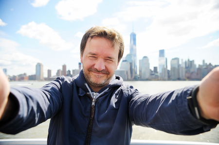 new age: Middle age man making a self portrait (selfie) with Manhattan skyscrapers in New York City