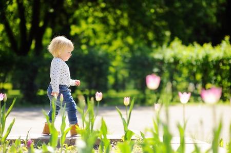 gente saltando: Muchacho del niño que camina en el parque en el día de primavera o verano