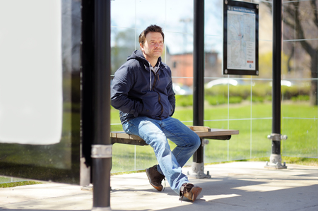 Middle age man sitting on bench on bus stop 免版税图像 - 53289699