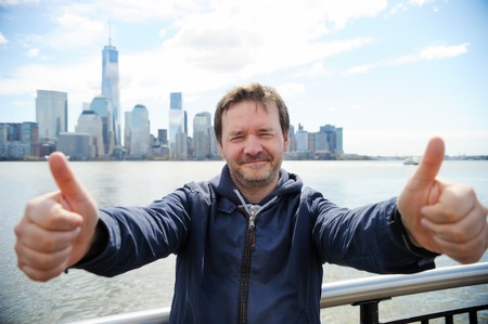 new age: Happy middle age man giving thumbs up sign with Manhattan skyscrapers in New York City Stock Photo