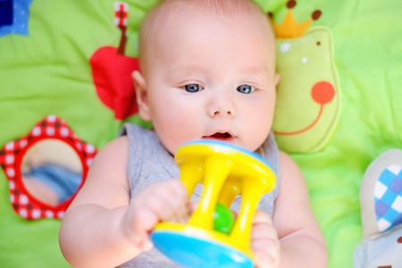 0 6 months: Portrait of little baby play with bright toy