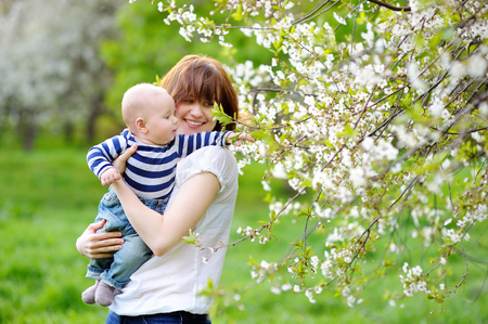 Little baby boy with her young mother in the blossom garden Stock Photo
