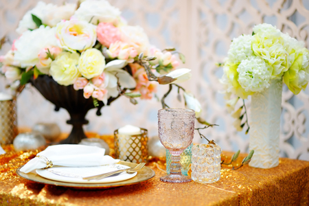 Stylish gold table set with natural flowers Stock Photo