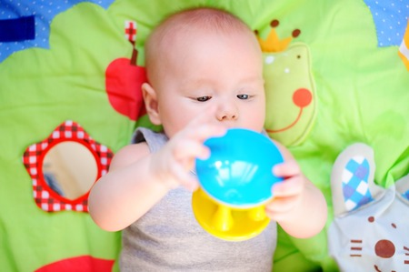 0 6 months: Little baby play with bright toy Stock Photo