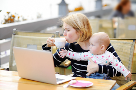impede: Tired young mother working oh her laptop, holding daughter and drinking coffee