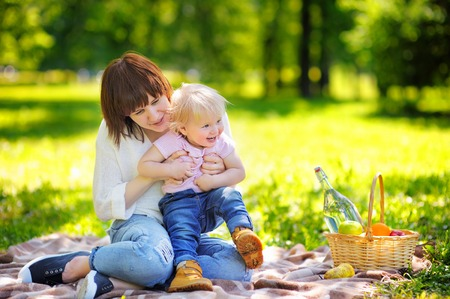 babysit: Beautiful young woman and her adorable little son having a picnic in sunny park Stock Photo