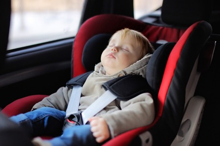 early childhood: Portrait of toddler boy sleeping in car seat