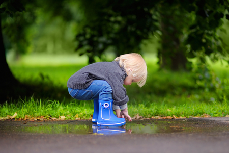 kid playing: Toddler playing with pool of water at the summer or autumn day Stock Photo