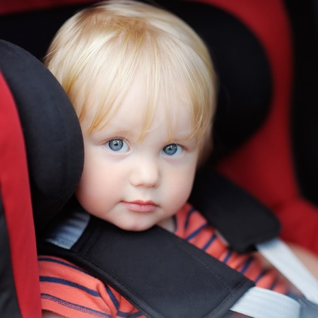 seat: Portrait of toddler boy sitting in car seat Stock Photo