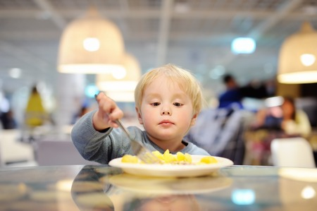 civilized: Cute toddler boy eating potatoes in indoors cafe