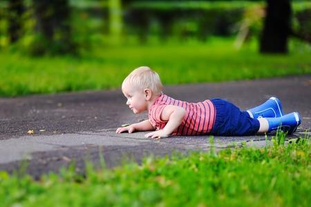 Portrait of cute toddler boy fell on park road