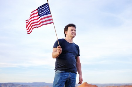 spunky: Middle age man holding american flag and looking on distance. Independence Day concept.
