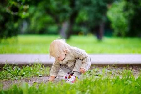 yard stick: Toddler playing at the park on the spring or summer day Stock Photo