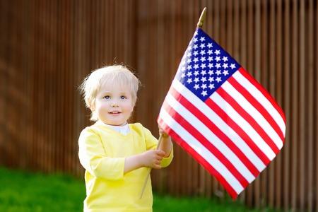 muchacho lindo del niño sosteniendo la bandera estadounidense. concepto del Día de la Independencia.