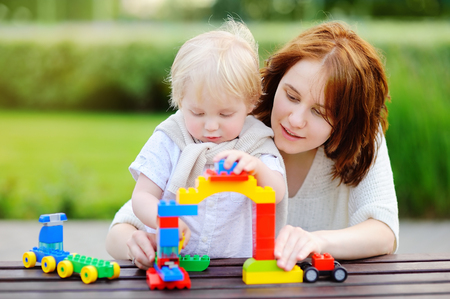 baby blocks: Young woman with his toddler son playing with colorful plastic blocks