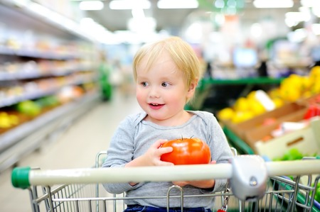 produce departments: Cute toddler boy sitting in the shopping cart in a food store or a supermarket
