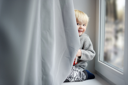 toddler boy: Toddler boy playing on the window sill at home