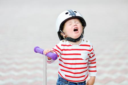Al aire libre retrato de niño llorando niño en el casco de seguridad con la vespa Foto de archivo