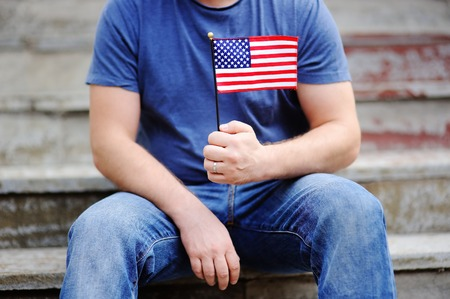 solemnity: Handsome man holding american flag. Independence Day concept.