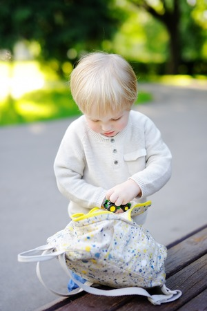 assiduous: Cute toddler boy putting his toys in backpack outdoors