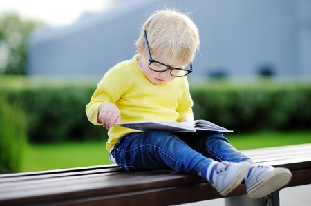 Cute toddler boy reading a book outdoors on warm summer day. Back to school concept Foto de archivo