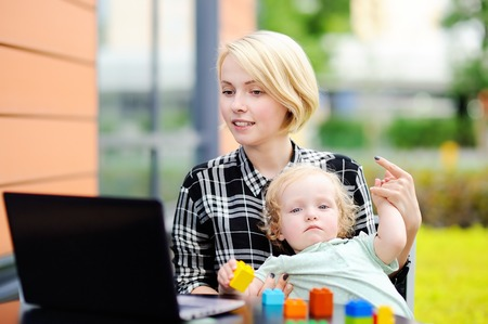hinder: Young mother working oh her laptop and holding her sad toddler daughter